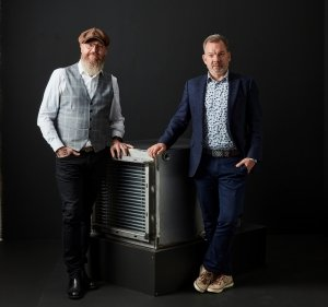 Two men standing next to a heat exchanger. Photo.