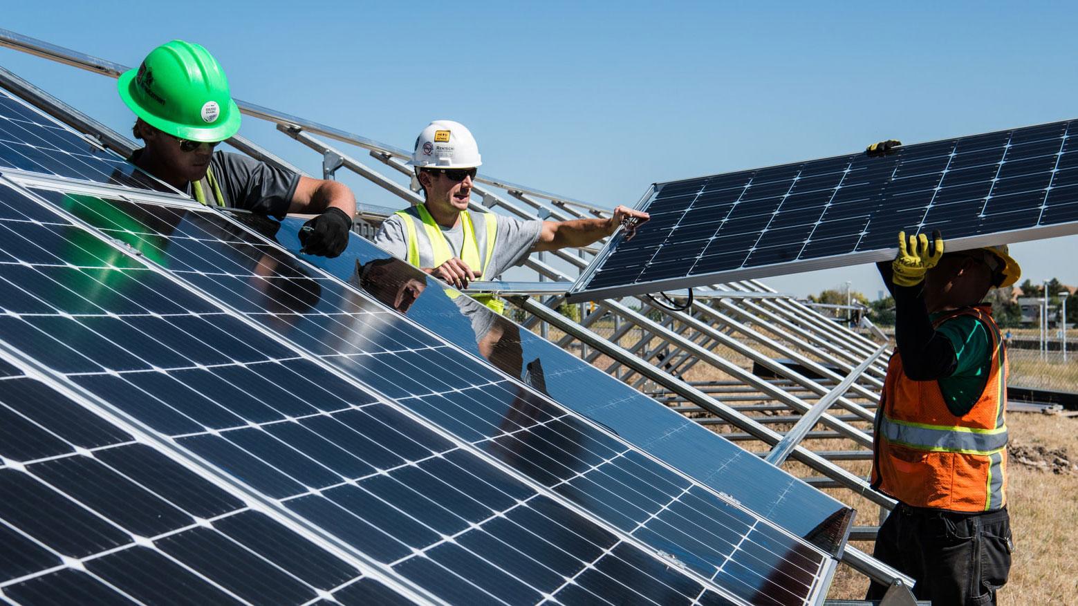 Three men installing solar panels. Photo.